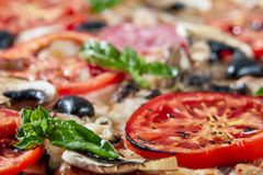 Closeup of pizza with salami, tomatoes and olives stock images
