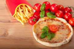 Closeup of pizza withfrench fries, tomatoes, cheese and basil on wooden background Stock Photo