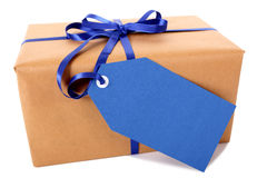Closeup of plain brown paper package or parcel, blue gift tag or label isolated on white background. Plain brown paper package or parcel, blue gift tag or label Royalty Free Stock Images
