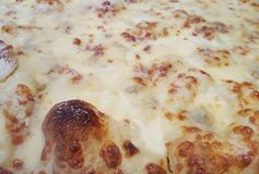 Closeup of bubbling cheese pizza. Closeup of a plain cooked lightly browned bubbling cheese pizza with no tomato sauce stock images