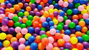 Closeup of plastic balls on surface of pool. Colorful textured background created by a large number of colorful plastic balls floating on the surface of a Royalty Free Stock Image