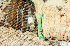 Closeup of plastic orange safety net used as security fence on the street district heating pipeline system excavation site to prot. Ect people of falling in to stock image