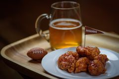 Closeup of plate of boneless honey bbq hot wings on plate with m. Macro close up of plate of boneless hot wings and glass mug of beer for big football game Stock Images