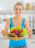 Closeup on plate of fruits giving by smiling woman Royalty Free Stock Images