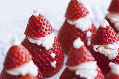 Santa Claus Strawberries. Closeup of plate full of strawberries with icing decorated to look like little Santas stock image