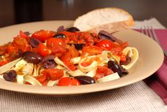 Closeup of a plate of pasta puttanesca with wine and bread. A closeup of a plate of pasta puttanesca with wine and bread royalty free stock images