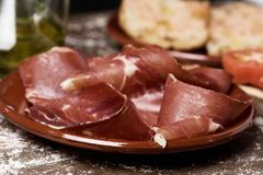 Serrano ham and catalan pa amb tomaquet. Closeup of a plate with some slices of serrano ham on a rustic wooden table, next to a plate with typical catalan pa amb Stock Image