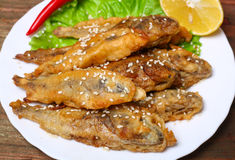 Closeup of a plate with spanish boquerones fritos, battered and fried anchovies typical in Spain, on a rustic wooden table Stock Photos