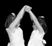 Closeup of playful twins with hands joined Royalty Free Stock Image