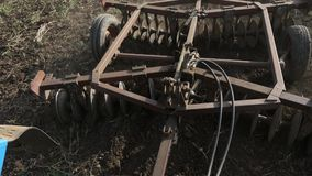 Closeup of plow attached to a tractor plowing a field. Real working process at organic eco farm. View from cabin, 4k stock video footage