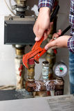 Closeup of plumber turning heating system valve with red pliers Stock Image