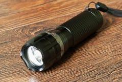 Closeup pocket LED flashlight on dark background stock image