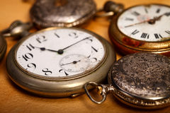 Closeup pocket watches. Closeup picture of different sizes pocket watches. Old paper background Stock Photography