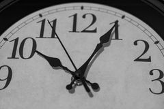 Five past ten. Closeup on the pointers of a clock marking five minutes after ten o'clock - black and white rendering. The main focus is on the hour and minute Royalty Free Stock Images