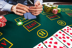 Closeup of poker player with playing cards and chips Stock Images