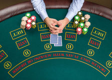 Closeup of poker player with playing cards and chips Royalty Free Stock Photography