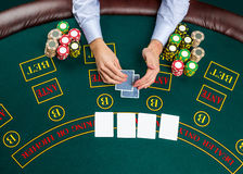 Closeup of poker player with playing cards and chips Royalty Free Stock Photo
