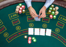 Closeup of poker player with playing cards and chips Stock Photos
