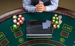 Closeup of poker player with playing cards, laptop and chips Royalty Free Stock Photo