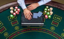 Closeup of poker player with playing cards, laptop and chips Royalty Free Stock Images