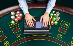 Closeup of poker player with playing cards, laptop and chips Stock Photos