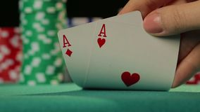 Closeup of poker player's hand checking cards, holding two aces, chance to win. Stock footage stock video footage