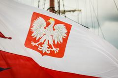 Closeup of polish national flag with emblem. Closeup of polish national flag with eagle emblem on ship in marine Royalty Free Stock Photos