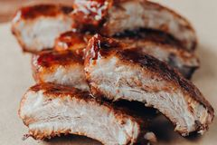 Delicious barbecued ribs seasoned with a spicy basting sauce. Closeup of pork ribs grilled with BBQ sauce and caramelized in honey stock photography