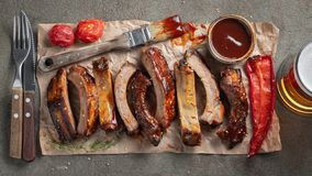 Closeup of pork ribs grilled with BBQ sauce and caramelized in honey. Tasty snack to beer on a paper for filing on dark. Concrete background. Top view. Flat lay royalty free stock image