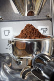 Closeup of a portafilter filled with fresh ground coffee under g Stock Photography