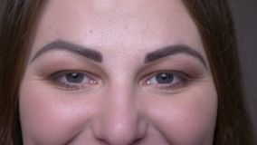 Closeup portarit of young overweight caucasian female face with eyes looking at camera with smiling facial expression. With background isolated on gray stock video