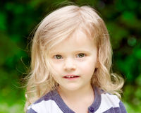 Closeup portrait of an adorable little girl with blond curly hair. In summer day royalty free stock image