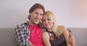 Closeup portrait of adult affectionate caucasian couple hugging smiling happily looking at camera sitting on sofa. Indoors in cozy apartment stock video footage