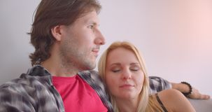Closeup portrait of adult affectionate caucasian couple hugging tenderly sitting on sofa indoors in cozy apartment.  stock footage