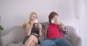 Closeup portrait of adult attractive caucasian couple drinking coffee sitting on couch indoors in apartment.  stock video footage