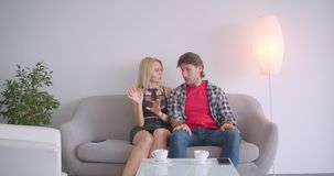 Closeup portrait of adult attractive caucasian couple having discussion sitting on sofa indoors in cozy apartment.  stock footage
