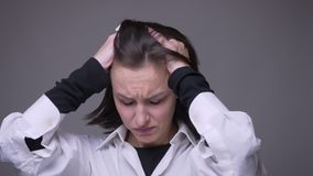 Closeup portrait of adult attractive caucasian female having a headache and being tired in front of the camera with. Background isolated on gray stock footage