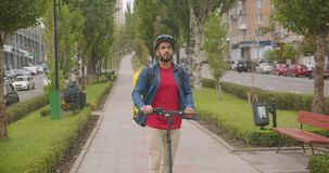 Closeup portrait of adult caucasian delivery man with backpack riding kick scooter in park city outdoors.  stock footage