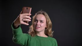 Closeup portrait of adult caucasian female having a video call on the phone and fixing her hair in front of the camera.  stock footage