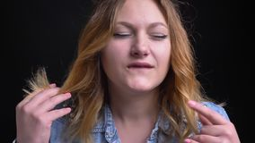 Closeup portrait of adult caucasian female making a tiger growl seductively biting her lip and playing with hair while. Looking at camera stock footage