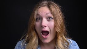 Closeup portrait of adult caucasian female with short blonde hair making different facial expressions and playing a fool. In front of the camera stock footage