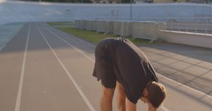 Closeup portrait of adult caucasian sporty male jogger stretching arms on the stadium in the urban city outdoors in the stock video footage