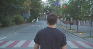Closeup portrait of adult caucasian sporty male jogger walking down the street in the urban city outdoors stock video