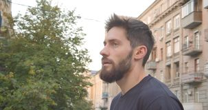 Closeup portrait of adult caucasian sporty male runner standing on the street looking at camera in the urban city stock footage