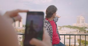 Closeup portrait of adult cheerful caucasian man being photographed on phone by his girlfriend standing on balcony with stock video footage