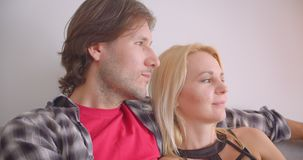 Closeup portrait of affectionate caucasian couple hugging tenderly smiling happily looking at camera sitting on sofa. Indoors in cozy apartment stock footage