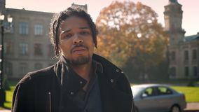 Closeup portrait of African-American guy with dreadlocks smoking and watching into camera on autumnal campus background. Closeup portrait of African-American stock video footage