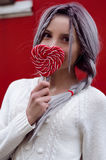 Closeup portrait amazing girl in the white warm woolen sweater with gray silver hair with red and white lollipop Stock Photography