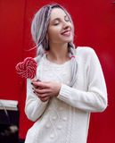 Closeup portrait amazing girl in the white warm woolen sweater with gray silver hair with red and white lollipop Royalty Free Stock Photos