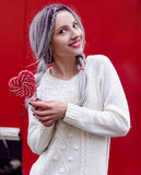 Closeup portrait amazing girl in the white warm woolen sweater with gray silver hair with red and white lollipop Royalty Free Stock Photo